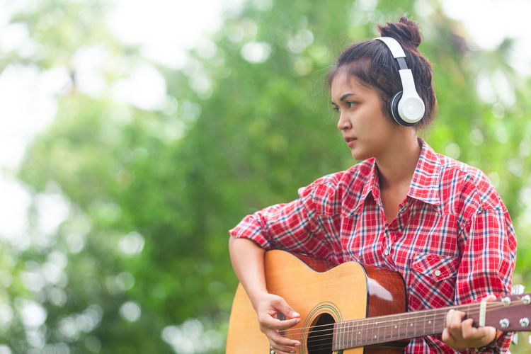 Headphones Acoustic Guitar Adult Artist Arts Culture And Entertainment Enjoyment Guitar Hairstyle Headphones Leisure Activity Lifestyles Listening Model Asian Music Musical Instrument Musician One Person Performance Playing Plucking An Instrument Skill  String Instrument Women Young Adult Young Women