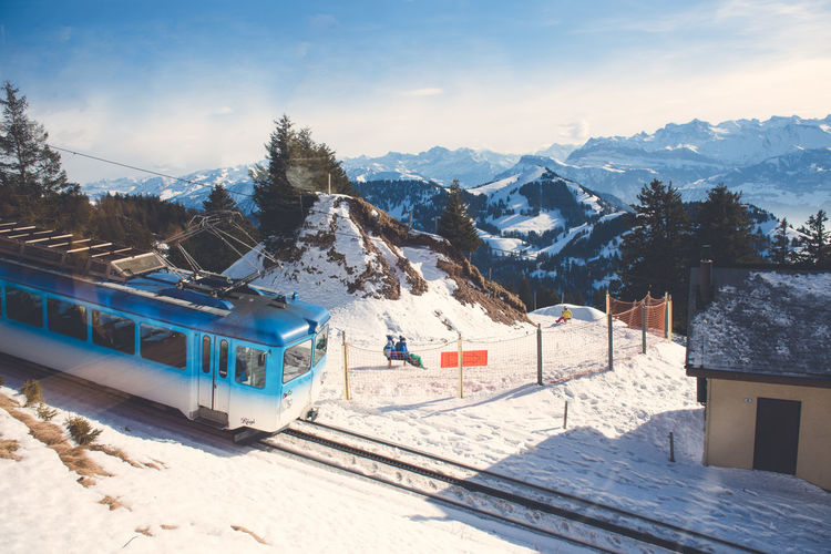 High angle view of blue train by snowcapped mountains against sky