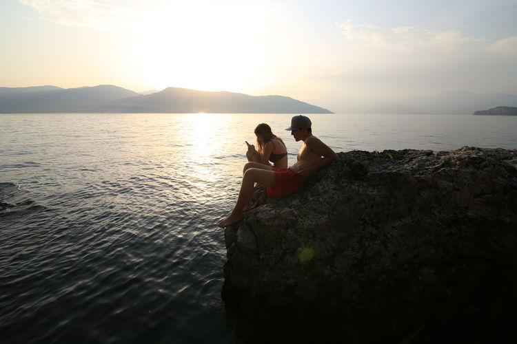 Connected By Travel Bonding Friendship Leisure Activity Lifestyles Outdoors Relaxation Sea Sky Sunset Togetherness Two People Water