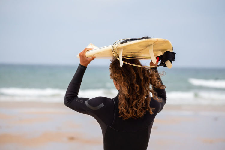 Rear view of man carrying surfboard at beach