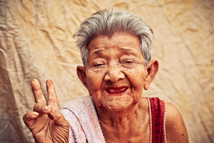 Old woman smiled and raised two fingers. Smiled Adult Adults Only Close-up Day Happiness Human Body Part Human Hand Old Woman One Person Outdoors People Portrait Real People Senior Adult Senior Women Smiling Wrinkled This Is Aging