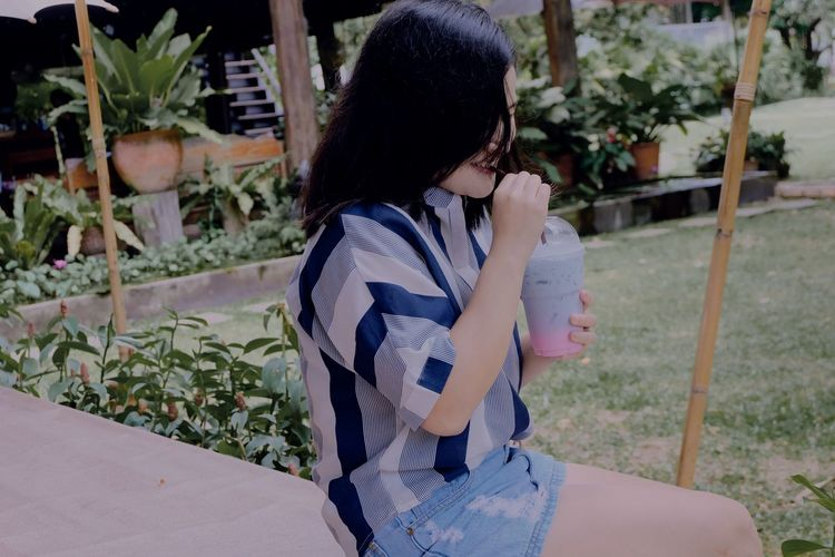 Side view of young woman drinking smoothie while sitting against plants in park