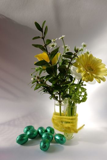 Easter eggs by flower vase against wall