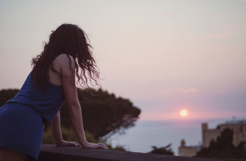 Side view of woman by retaining wall against sky during sunset