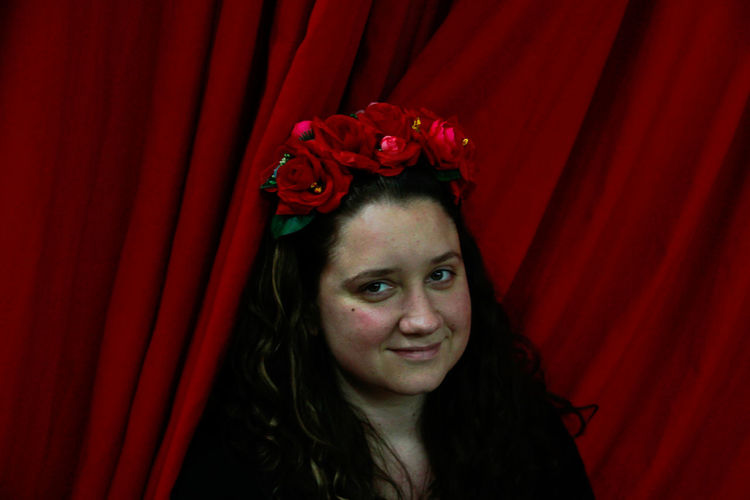 Portrait of beautiful young woman with red flower against curtain