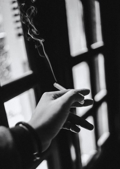 Close-Up Of Human Hand Holding Cigarette