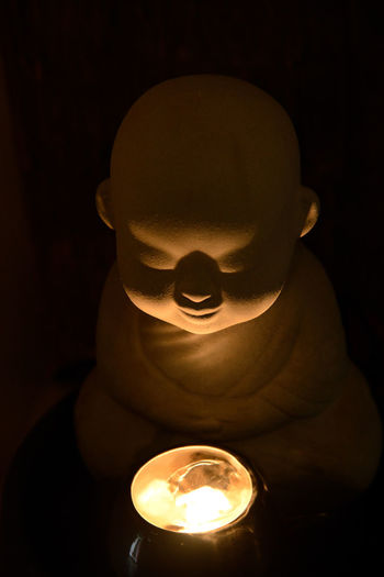 A monk pray for blessing with a candle Sami Sami People Candle Dark Darkness Light Pray Acolyte Black Background Blessing Buddhism Face Fire Indoors  Monk  Religion Stone Statue Yellow