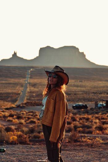 Portrait of woman wearing sunglasses standing on landscape