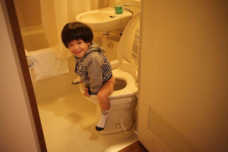 Cute Boy Sitting On Toilet Bowl At Bathroom
