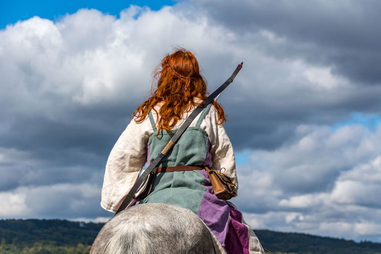 Rear View Of Woman Sitting On Horse Against Cloudy Sky