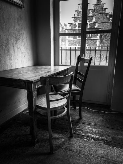 Empty chairs and table against window in house