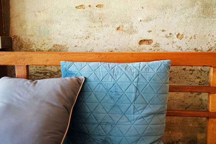 Close-up of cushion against wall at home