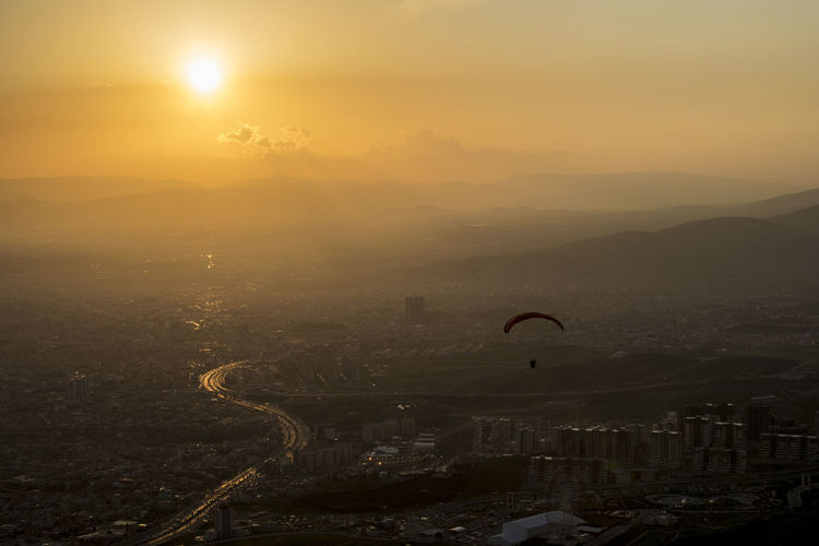 Person paragliding over city against sky during sunrise
