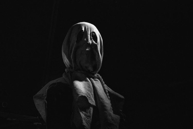 Person in mask against black background