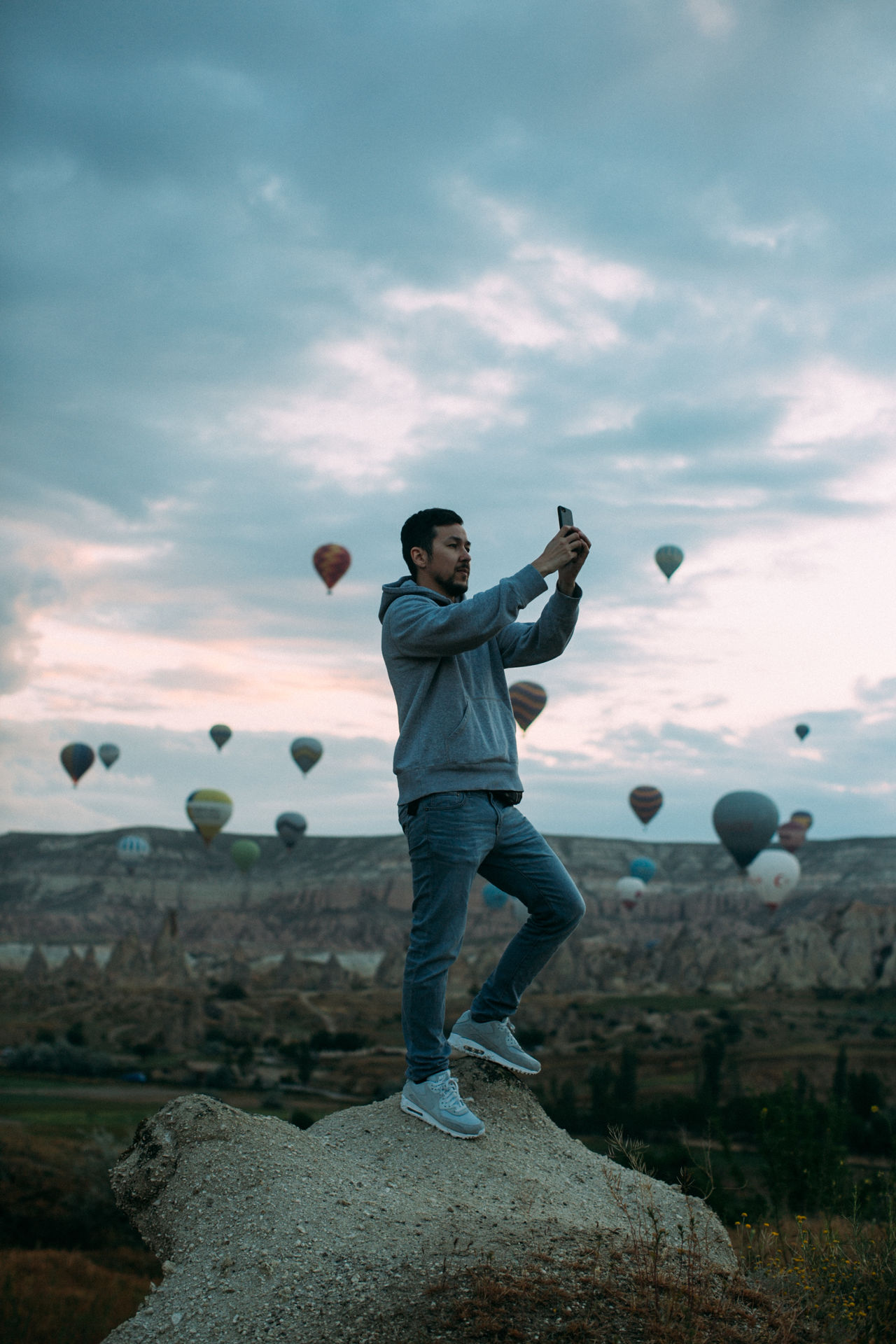 Full length of man photographing through mobile phone with hot air balloons in background during sunset