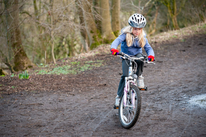 Girl riding bicycle on dirt road in forest