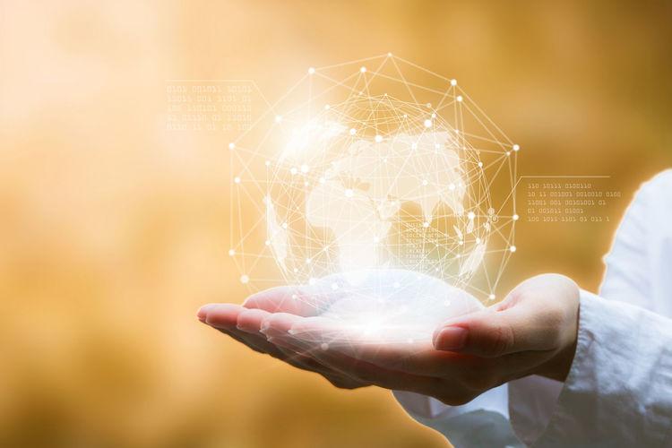 Digital composite image of hands holding globe