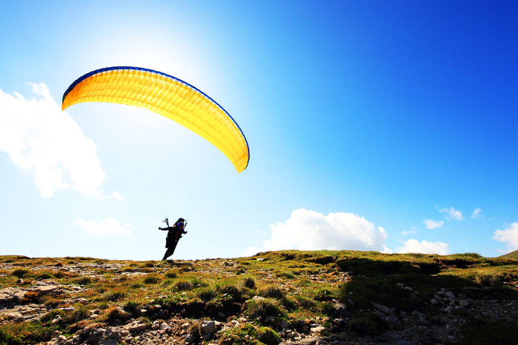 Man with parachute on field against sky