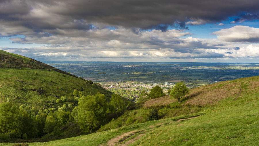 View towards Great Malvern from the Malvern Hills, ,UK English Countryside Malvern Hills Beauty In Nature Cloud - Sky Day England Environment Grass Great Malvern Green Color Growth Land Landscape Mountain Nature No People Non-urban Scene Outdoors Plant Rolling Landscape Scenics - Nature Sky Tranquil Scene Tranquility Tree Uk Worcestershire