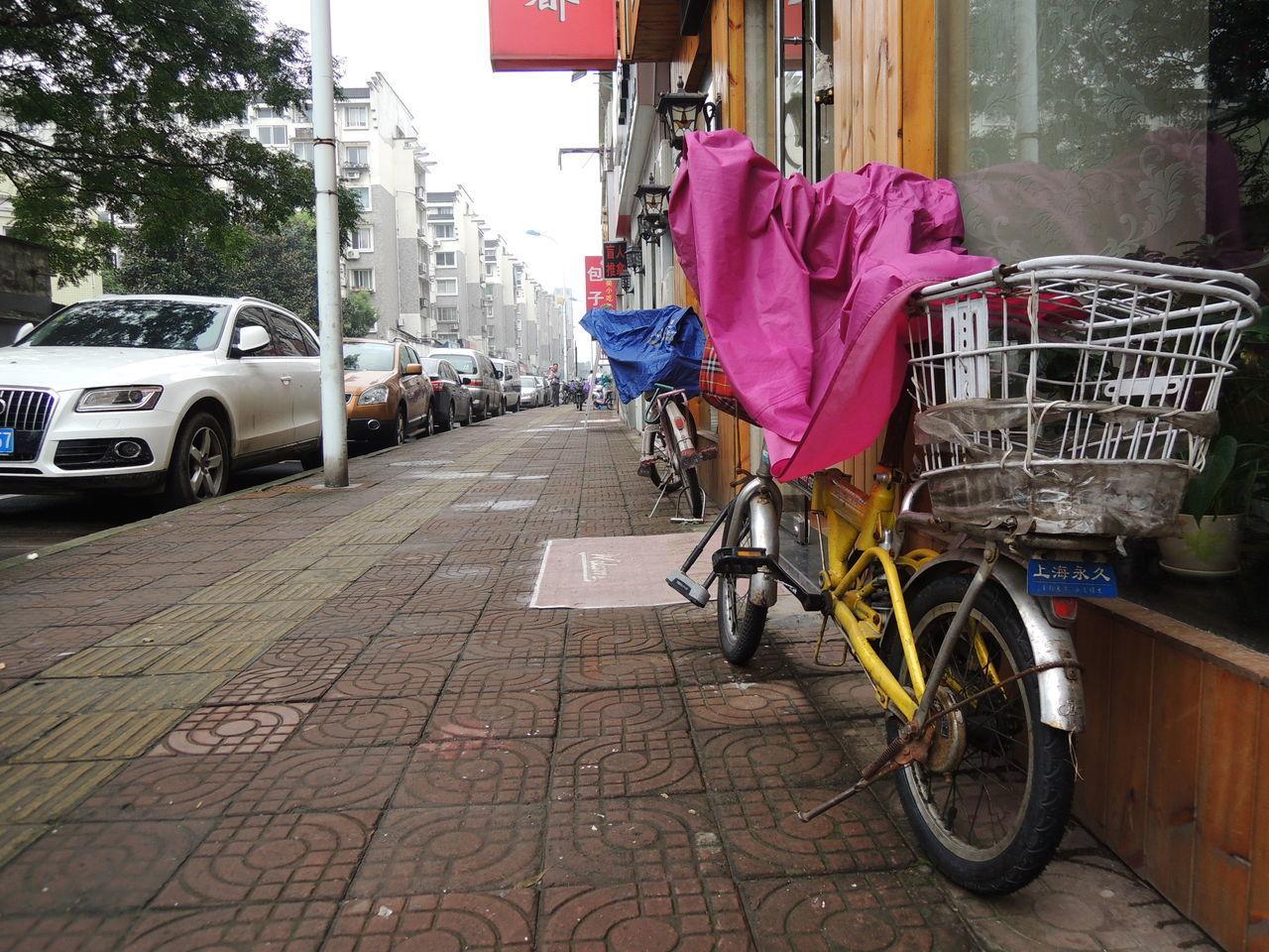 BICYCLE ON SIDEWALK BY ROAD AGAINST BUILDINGS