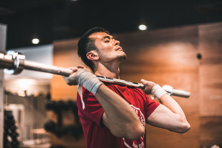 Tzei Wei Lim - V One Person Focus On Foreground Real People Waist Up Young Men Young Adult Men Indoors  Performance Sport Lifestyles Standing Holding Looking Away Leisure Activity Adult Skill  Arms Raised Barbell Muscles Muscular Build Red Athlete athleisure Weightlifting