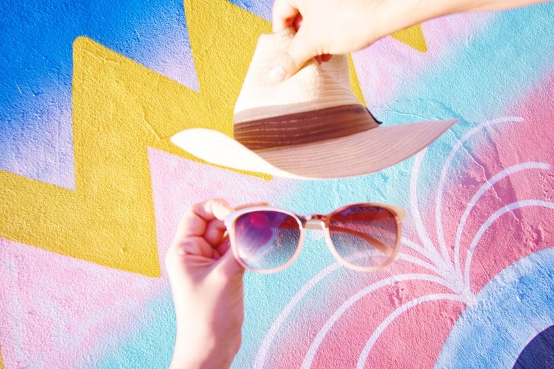 Cropped hands holding hat and sunglasses against patterned wall