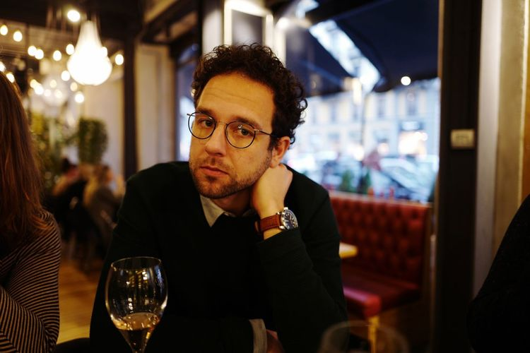EyeEm Selects One Person Eyeglasses  Real People Night Wine Indoors  Focus On Foreground Sitting Restaurant Wineglass Illuminated Lifestyles Looking At Camera Portrait Headshot Close-up Adult Adults Only People