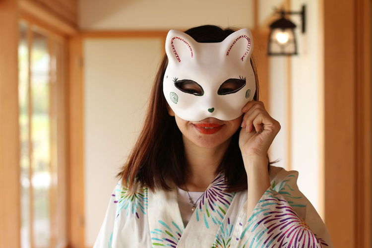 Portrait of smiling young woman wearing mask at home