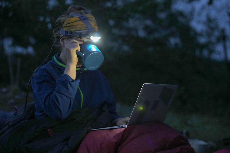 caucasian female hiker working on her laptop at night during wild camping, portable technology concept Backpacking Camping Dark Females Freedom Headlamp Hiking Nature Reading Travel Trekking Working Adventure Battery Communication Computer Concentration Connection Dark Drink Drinking Evening Hobby Holding Internet Journal Land Laptop Leisure Activity Looking Night One Person Outdoors People Portability Portable Information Device Real People Sitting Technology Using Laptop Watching Wireless Technology Women