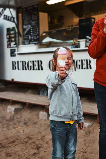 Little girl holding her ice cream in front of her face standing in front of food truck