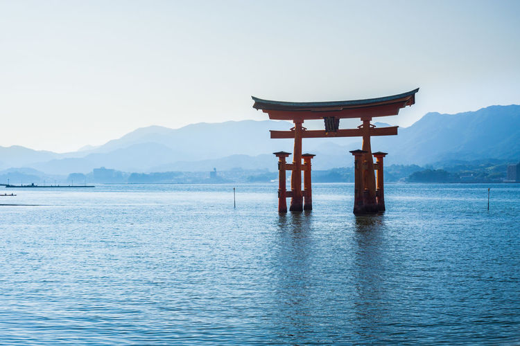 Itsukushima temple in bay against sky