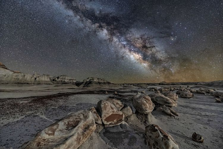 Scenic view of rocks at beach against sky at night