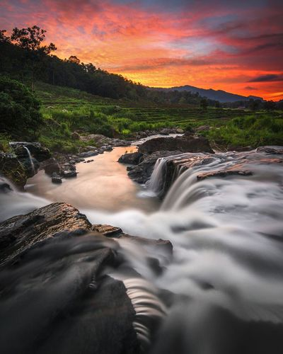 Scenic view of stream against sky during sunset
