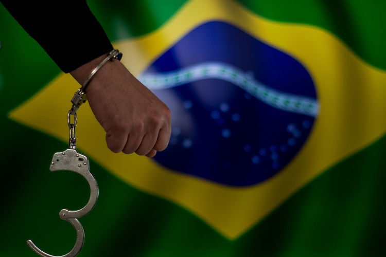 Cropped hand with handcuffs against brazilian flag