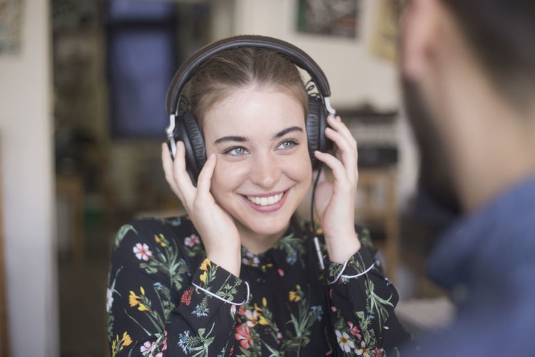 Smiling young woman listening to music in a record store