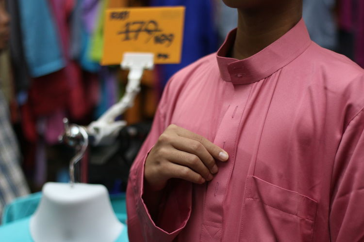 Midsection of boy wearing peach shirt while standing in shop