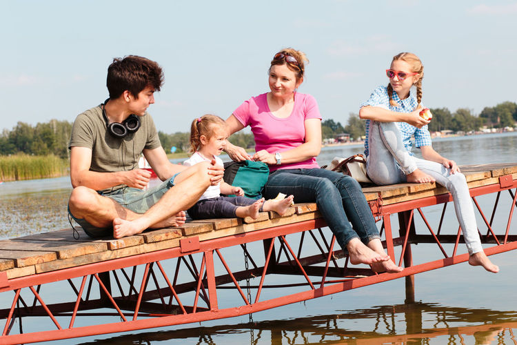 Family spending vacation time together having a snack sitting on jetty over the lake on sunny day in the summertime Family Moments Recreation  Relaxing Summertime Vacation Time Vacations Boy Childhood Family Time Girl Joy Joy Of Life Leisure Leisure Activity Lifestyles Outdoors People Real People Recreational Pursuit Relaxation Relaxing Time Summer Summer Vibes Togetherness