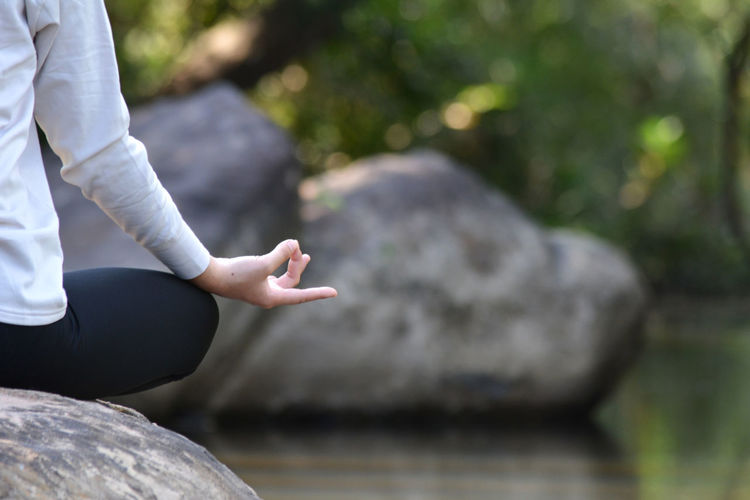Midsection of woman doing yoga on rock by lake