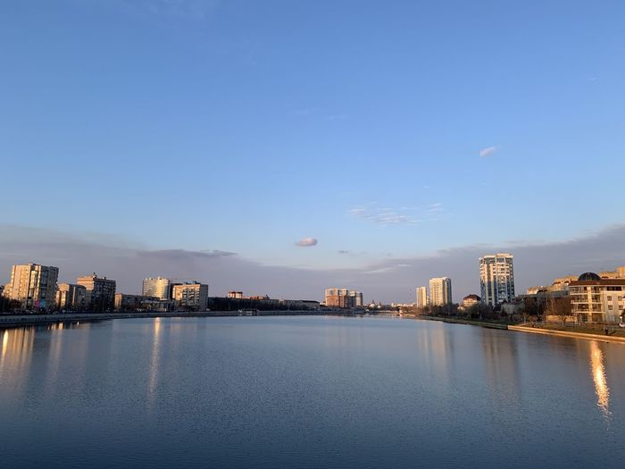 Scenic view of river by buildings against blue sky
