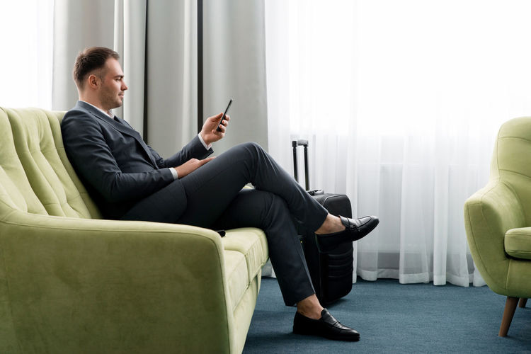 Businessman using mobile phone while sitting on sofa