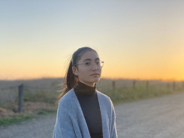 Portrait of young woman standing on land against sky during sunset