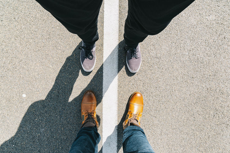 two people standing opposite at the street in leather and sneaker shoes, pov view, including copy space Business City Copy Space Jeans LINE Leather Life Man POV Teamwork Travel Across From Body Part First Person Perspective High Angle View Human Body Part Human Leg Low Section Opposite Personal Perspective Shoe Sneaker Standing Toward White