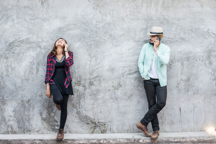 Friends talking on phones while standing against gray wall