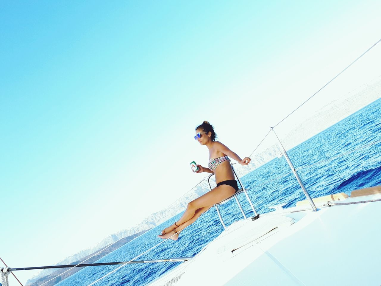 leisure activity, one person, sea, lifestyles, copy space, young adult, beauty in nature, transportation, real people, bikini, nautical vessel, nature, vacations, young women, summer, clear sky, beautiful woman, water, front view, outdoors, full length, day, sailing, sky, horizon over water, people