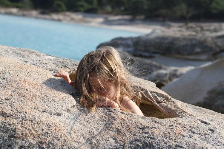 Girl peeking through rocks