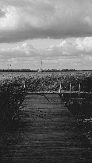 Wooden pier leading towards sea against sky