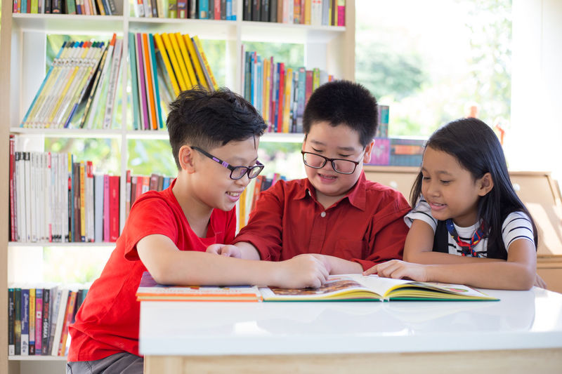 Group of students learning with book at library in school Student Back To School Book Bookshelf Boys Child Childhood Concentration Education Front View Girls Headshot Indoors  Innocence Learning Looking Looking Down Males  Men People Publication Student Study Studying Table