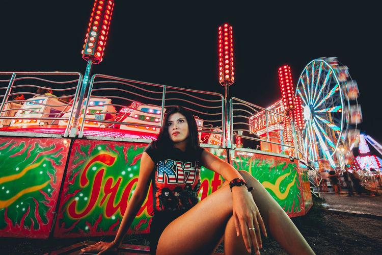 Woman sitting on illuminated carousel at amusement park