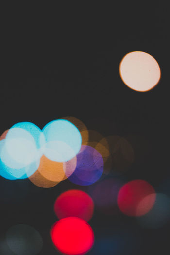 Defocused image of lights against sky at night