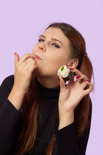 Portrait of woman holding ice cream against gray background